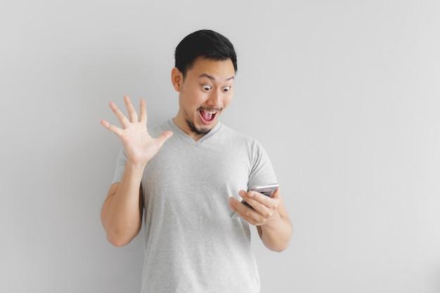 La faccia dell'uomo in maglietta grigia si fa sorprendere sullo smartphone. Foto Premium