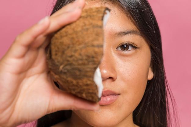 La faccia è coperta da metà della noce di cocco Foto Gratuite