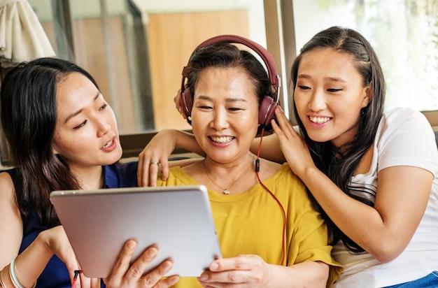 La famiglia asiatica sta usando insieme la compressa digitale Foto Gratuite