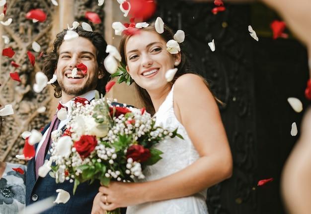 La famiglia che getta i petali di rosa al newly wed sposa e sposo Foto Premium