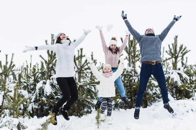 La famiglia che salta vicino agli abeti rossi Foto Gratuite