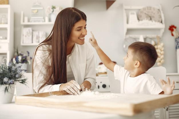 La famiglia che si siede in una cucina e cucina l'impasto per i biscotti Foto Gratuite