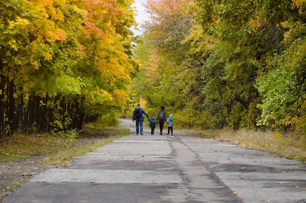 La famiglia con due figli sta camminando nel parco in autunno. Foto Premium