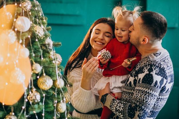 La famiglia con la piccola figlia che appende gioca sull'albero di natale Foto Gratuite