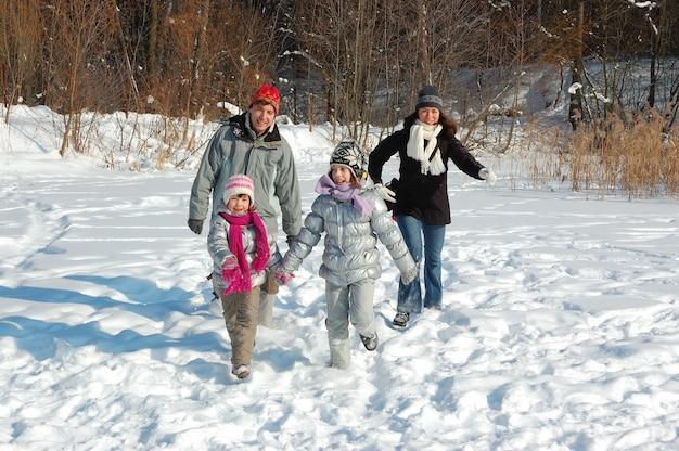 La famiglia felice cammina in inverno, divertendosi e giocando con la neve all'aperto durante il fine settimana di vacanza Foto Premium