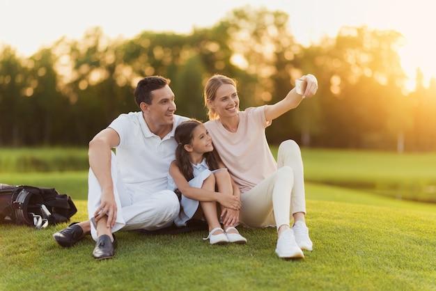 La famiglia felice ha resto dopo il golf prende selfie. Foto Premium