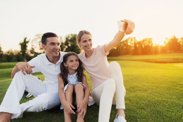 La famiglia felice prende selfie che si siede sul prato verde. Foto Premium