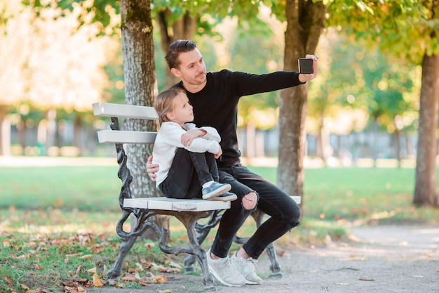 La famiglia felice si diverte a prendere selfie sulla bella giornata autunnale Foto Premium