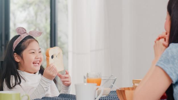 La famiglia giapponese asiatica fa colazione a casa. la figlia asiatica seleziona e gioca il sorriso di risata del pane con i genitori mentre mangia il cereale e il latte dei fiocchi di mais in ciotola sulla tavola in cucina moderna di mattina. Foto Gratuite