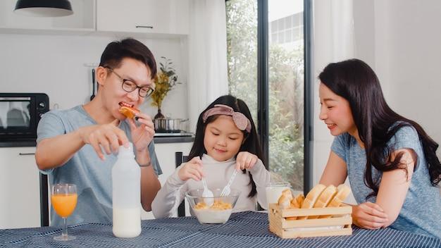 La famiglia giapponese asiatica fa colazione a casa. la mamma, il papà e la figlia asiatici che si sentono felici parlano insieme mentre mangiano il pane, i cereali dei fiocchi di mais e il latte in ciotola sulla tavola nella cucina di mattina. Foto Gratuite