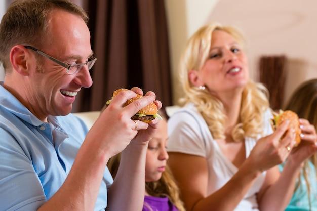 La famiglia mangia hamburger o fast food Foto Premium