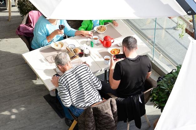 La famiglia si siede in un caffè al tavolo e mangia cibo Foto Premium