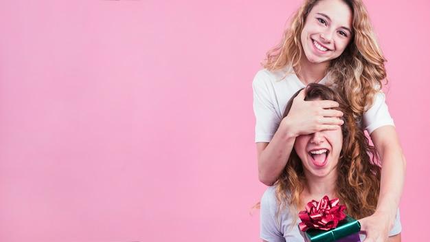 La femmina che copre gli occhi del suo amico che danno il contenitore di regalo contro fondo rosa Foto Gratuite