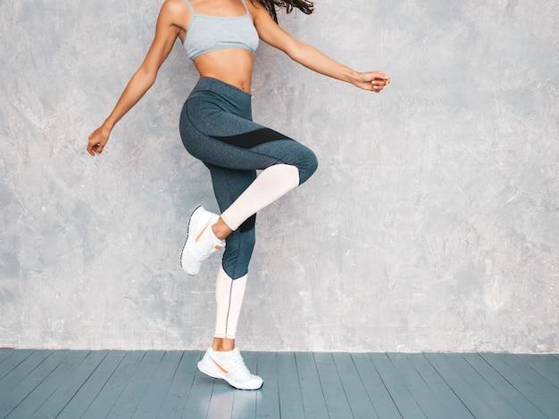 La femmina che salta nello studio vicino alla parete grigia Foto Gratuite
