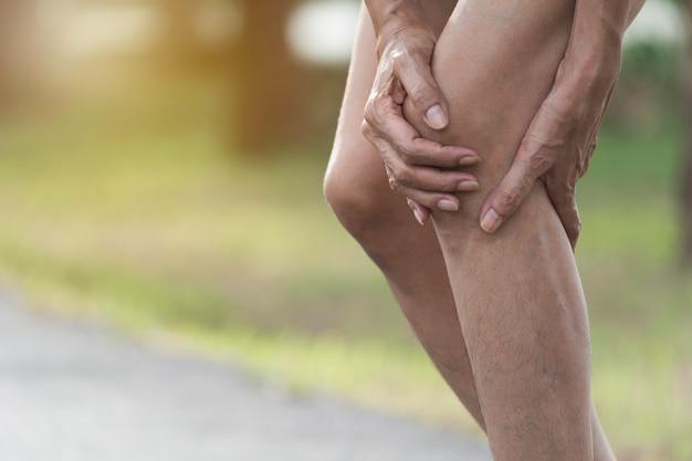 La femmina si aggrappa a una brutta gamba. il dolore alla gamba. salute e concetto doloroso. Foto Premium