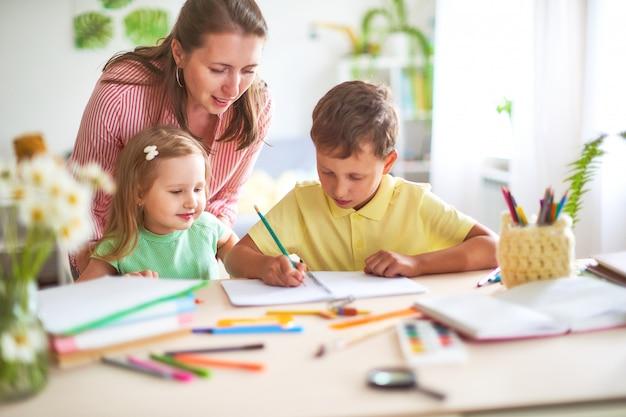 La figlia e il figlio della madre disegna la matita su un foglio di carta che si siede a casa alla tavola in una stanza luminosa. Foto Premium