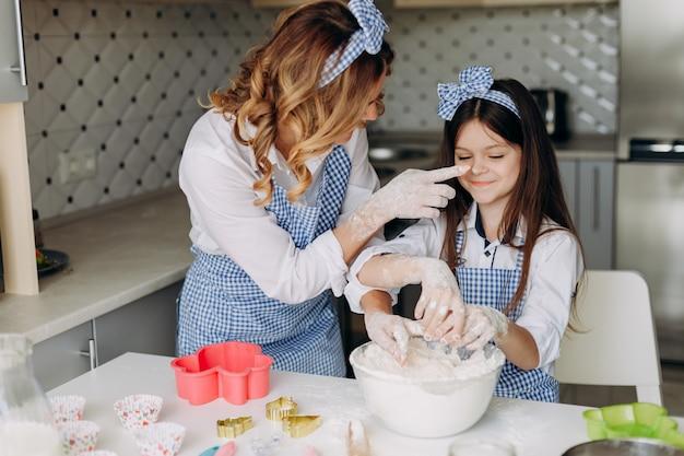 La figlia e sua madre in famiglia si divertono durante la cottura insieme. Foto Premium