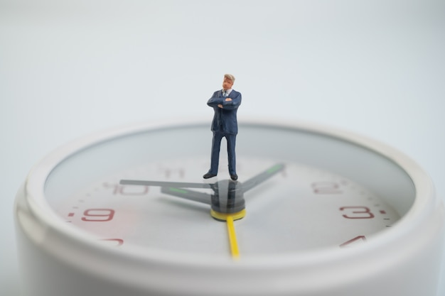 La figura degli uomini d'affari sta pensando e sta in piedi sul quadrante bianco accanto al quadrante che mostra l'ora. Foto Premium