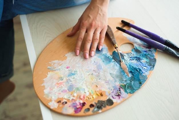 La fine della mano della donna mescola le pitture con la spazzola in tavolozza nella classe di arte Foto Premium