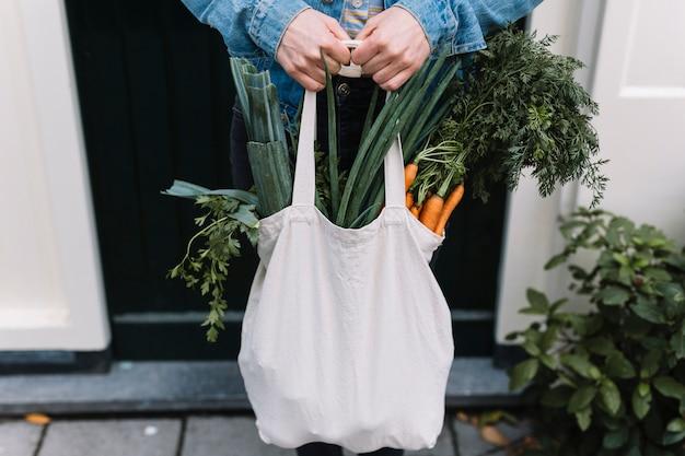 La fine di una persona che tiene il sacchetto di drogheria di acquisto bianco ha riempito di verdure Foto Gratuite
