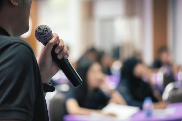 La fine sul conferenziere dell'uomo parla con il microfono nel fuoco selettivo. Foto Premium