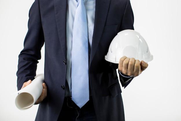 La fine sull'ingegnere in vestito convenzionale tiene il cappello duro del casco della sicurezza e il rotolo del modello Foto Premium