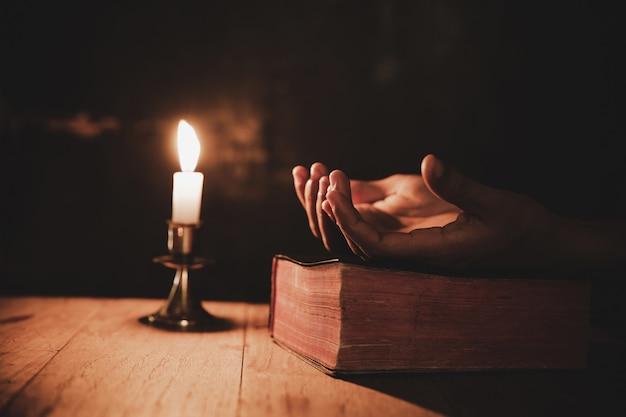 La fine sulla mano dell'uomo sta pregando nella chiesa con la candela accesa Foto Gratuite