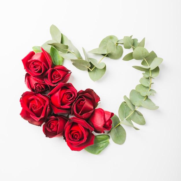 La forma del cuore fatta con le rose fiorisce e ramoscello su fondo bianco Foto Gratuite