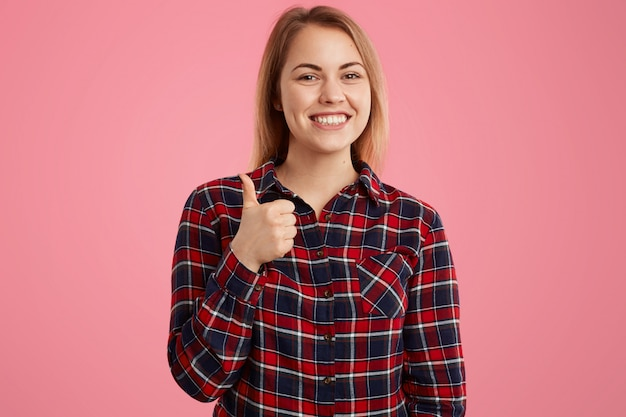 La foto della donna attraente con il sorriso a trentadue denti, vestita in camicia a scacchi, mantiene il pollice sollevato, dà l'approvazione a qualcosa Foto Gratuite