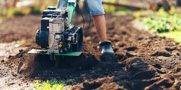 La foto vicina del giovane giardiniere dell'agricoltore coltiva il rototiller del suolo Foto Premium