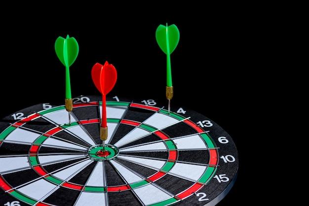 La freccia rossa e verde del dardo che colpisce il centro bersaglio è freccette isolata Foto Premium