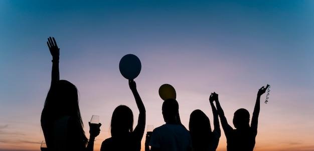 La gente che balla alla festa sul tetto all'alba Foto Gratuite