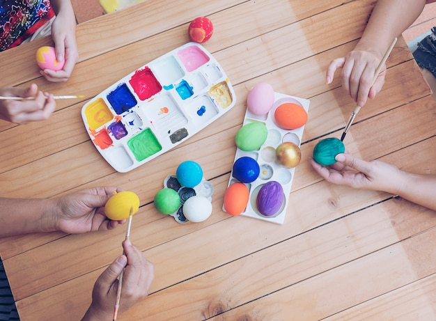 La gente che dipinge le uova di pasqua variopinte - concetto di celebrazione di festa di pasqua Foto Gratuite
