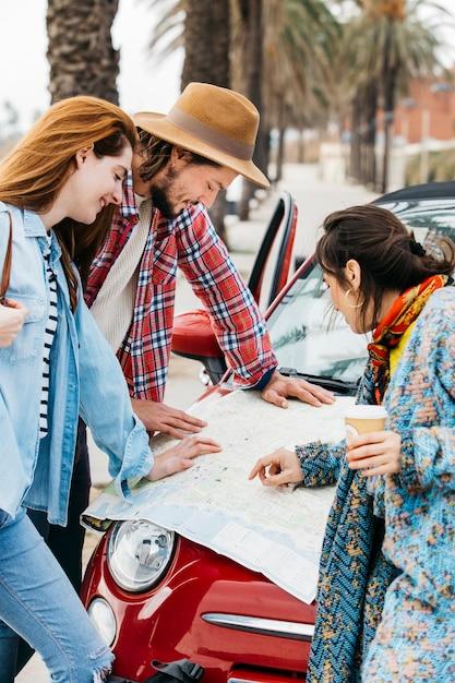 La gente che esamina la mappa stradale vicino all'automobile rossa Foto Gratuite