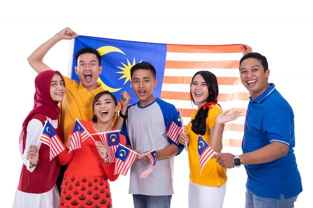 La gente che tiene la bandiera della malesia che celebra la festa dell'indipendenza Foto Premium
