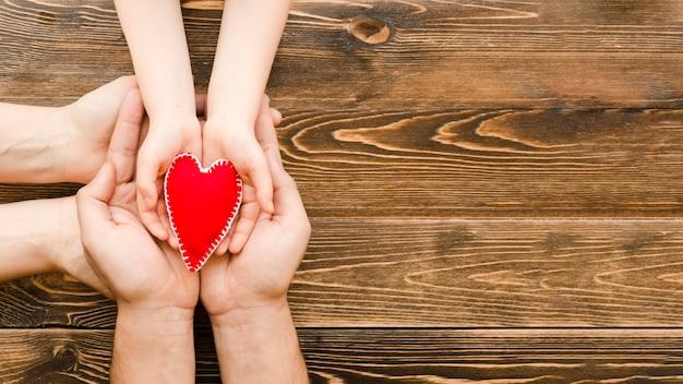 La gente che tiene un cuore rosso nelle mani con lo spazio della copia Foto Gratuite
