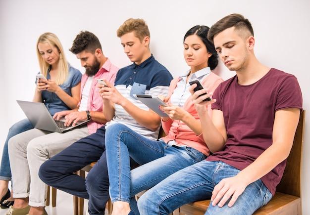 La gente è seduta nell'atrio a guardare i telefoni. Foto Premium