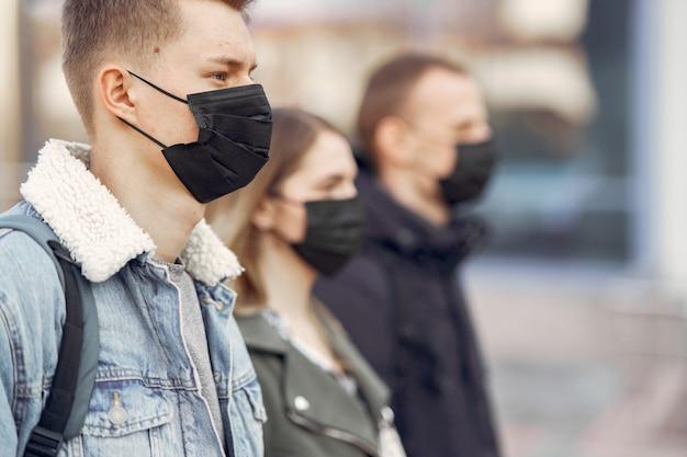La gente in maschera si trova sulla strada Foto Gratuite