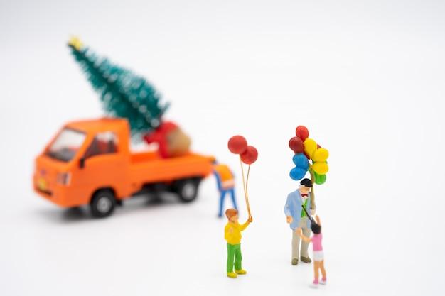 La gente miniatura della famiglia che sta sull'albero di natale celebra il natale Foto Premium