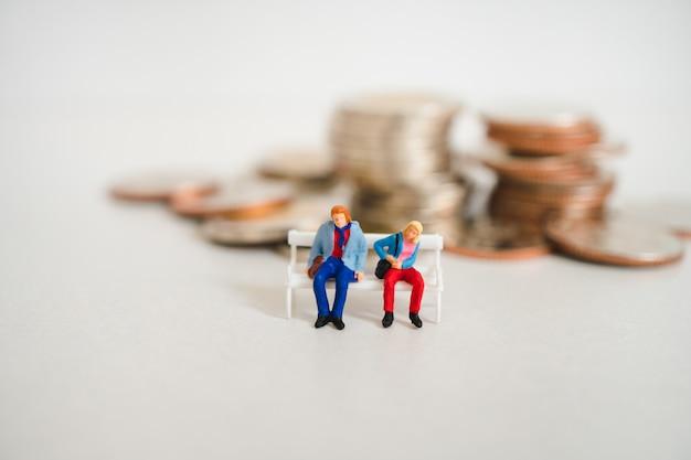 La gente miniatura, uomo delle coppie e donna che si siedono sulla pila conia il fondo Foto Premium