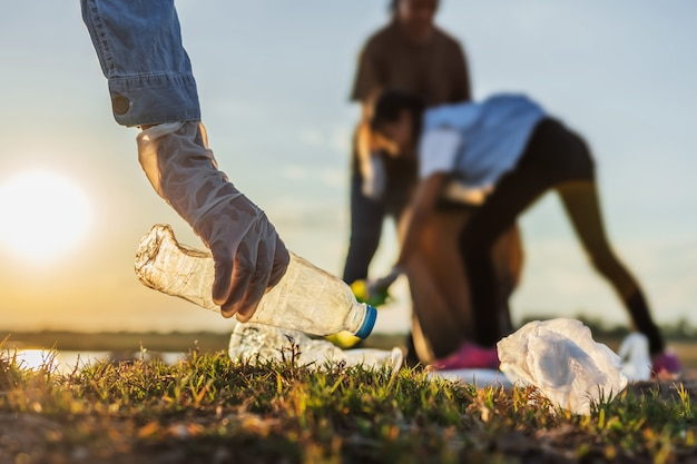 La gente si offre volontaria tenendo la bottiglia di plastica dell'immondizia nella borsa nera al fiume del parco nel tramonto Foto Premium