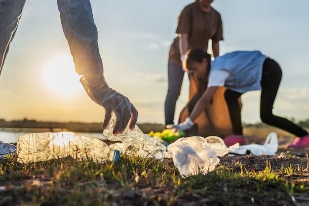 La gente si offre volontaria tenendo la bottiglia di plastica dell'immondizia nella borsa nera al parco vicino al fiume nel tramonto Foto Premium