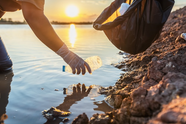 La gente si offre volontaria tenendo la bottiglia di plastica dell'immondizia nella borsa nera sul fiume nel tramonto Foto Premium