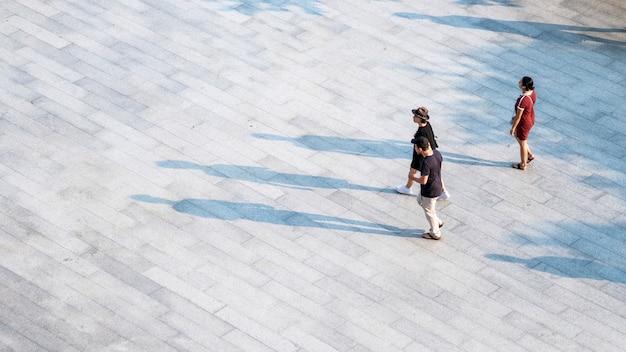 La gente vista aerea superiore cammina su cemento pedonale con sagoma nera. Foto Premium