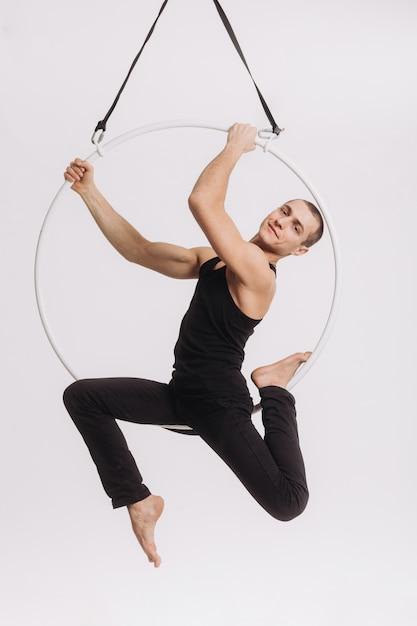 La ginnasta aerea maschio esegue l'elemento acrobatico nell'anello Foto Premium