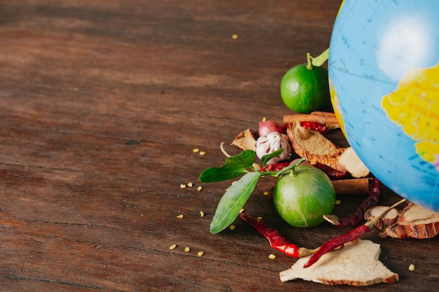 La giornata mondiale dell'alimentazione, una spezia piena di auto e colori freschi posizionati su un globo simulato su un pavimento di legno marrone. Foto Gratuite