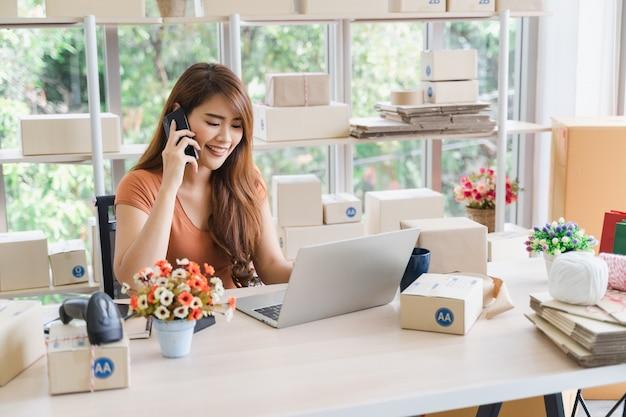La giovane bella donna asiatica felice di affari nell'abbigliamento casual con la faccina sta richiedendo riceve gli ordini del cliente con il computer portatile al suo ufficio domestico startup, concetto della pmi Foto Premium