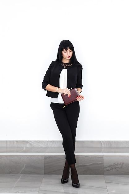 La giovane bella donna castana seria con un taccuino si è vestita in un vestito nero che sta contro la parete bianca in ufficio. Foto Premium