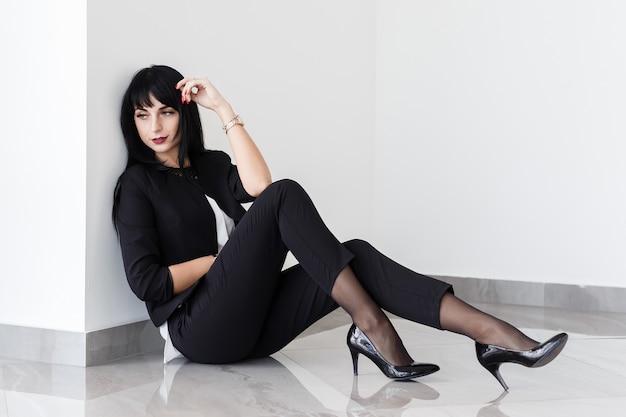La giovane bella donna castana triste si è vestita in un vestito nero che si siede su un pavimento in un ufficio. Foto Premium