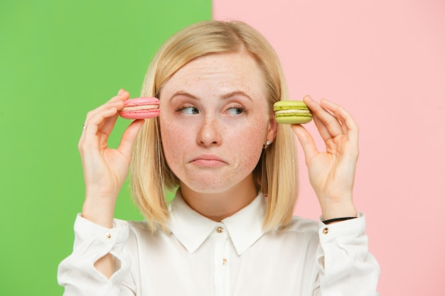 La giovane bella donna che tiene i maccheroni pasticceria in sue mani, sopra d'avanguardia colorato allo studio. Foto Gratuite